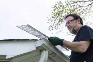 Professional installing gutter protection
